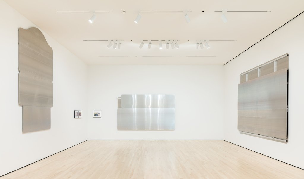 A gallery hung with large aluminum panels