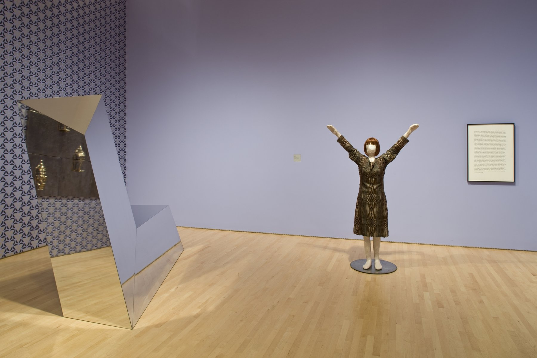A sculpture of a woman with her hands raise din the air next to a reflective geometric sculpture and a framed block of text