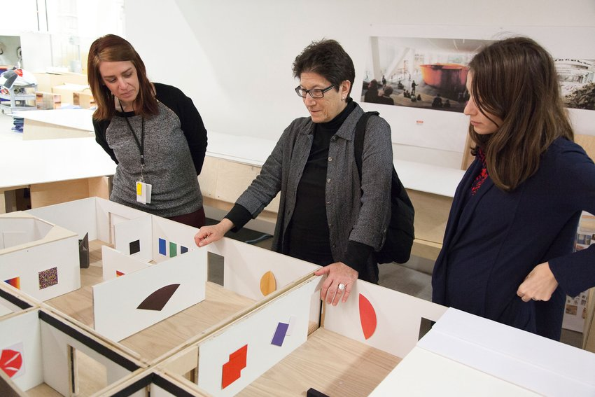 Three women look down into a model gallery with miniature paintings installed throughout