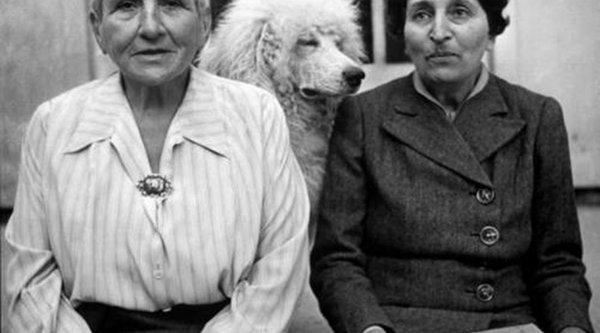 two women sitting with a poodle behind them