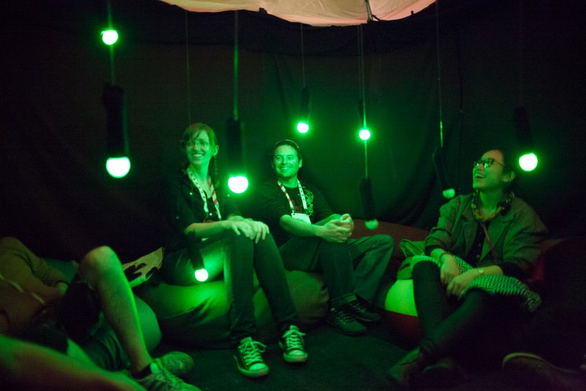 Four people sitting on bean bag chairs in an enclosed tent-like space with green lights hanging from above