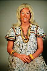 Cindy Sherman, fake tan and blonde wig sitting down