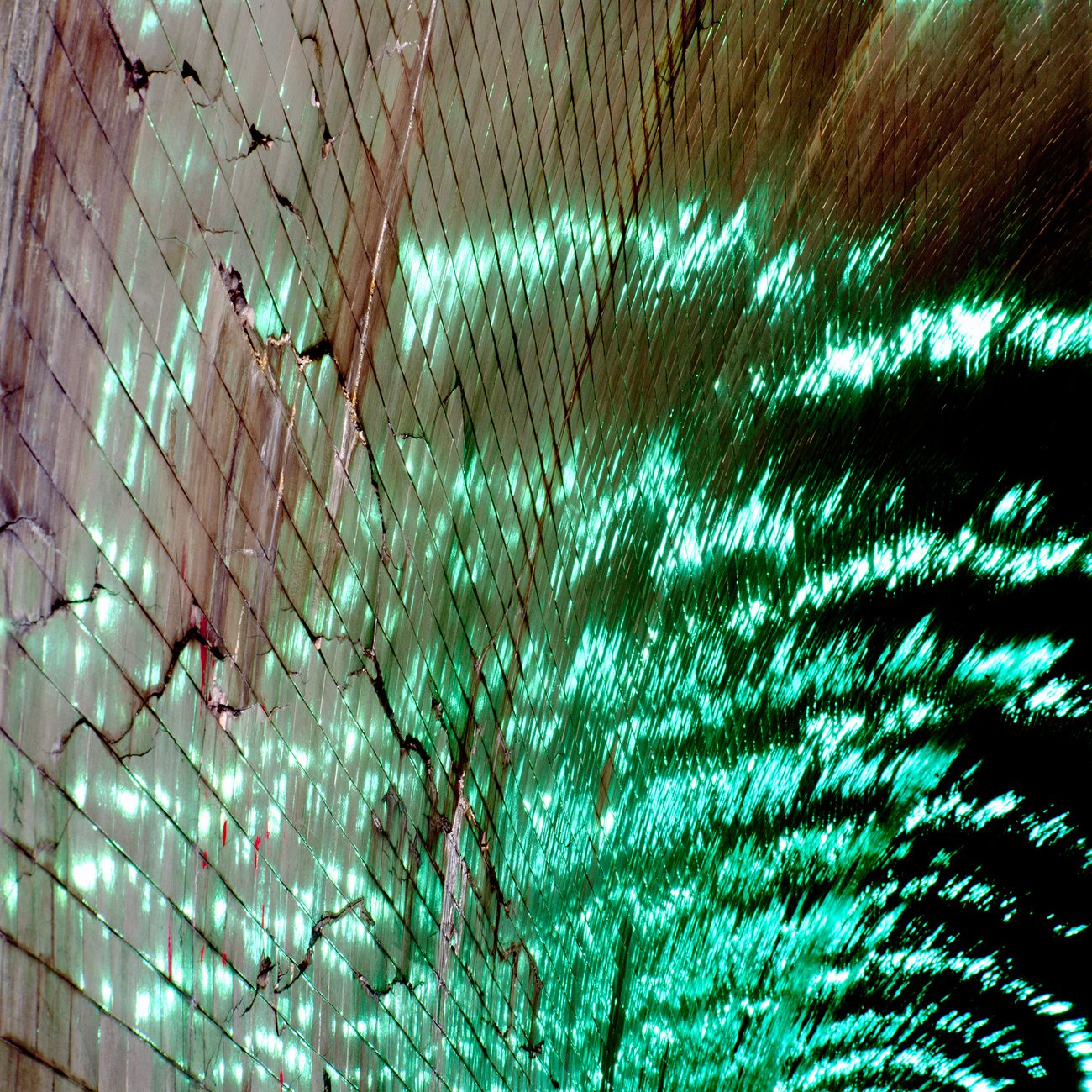 Reflection of water and green lights on the ceiling of a tunnel.