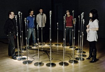 five people standing around circle of microphones