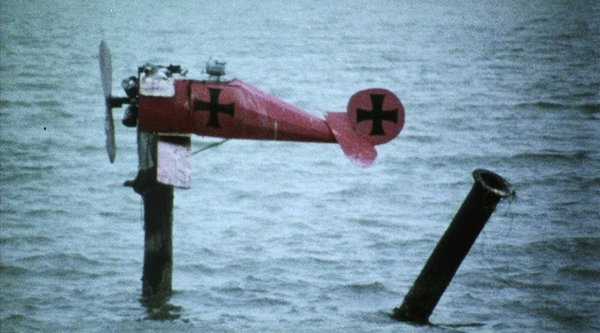small red propeller laying in ocean