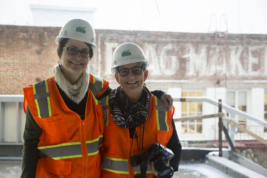 Two women in glasses, hard hats, and bright orange constrction vests stand arm in arm