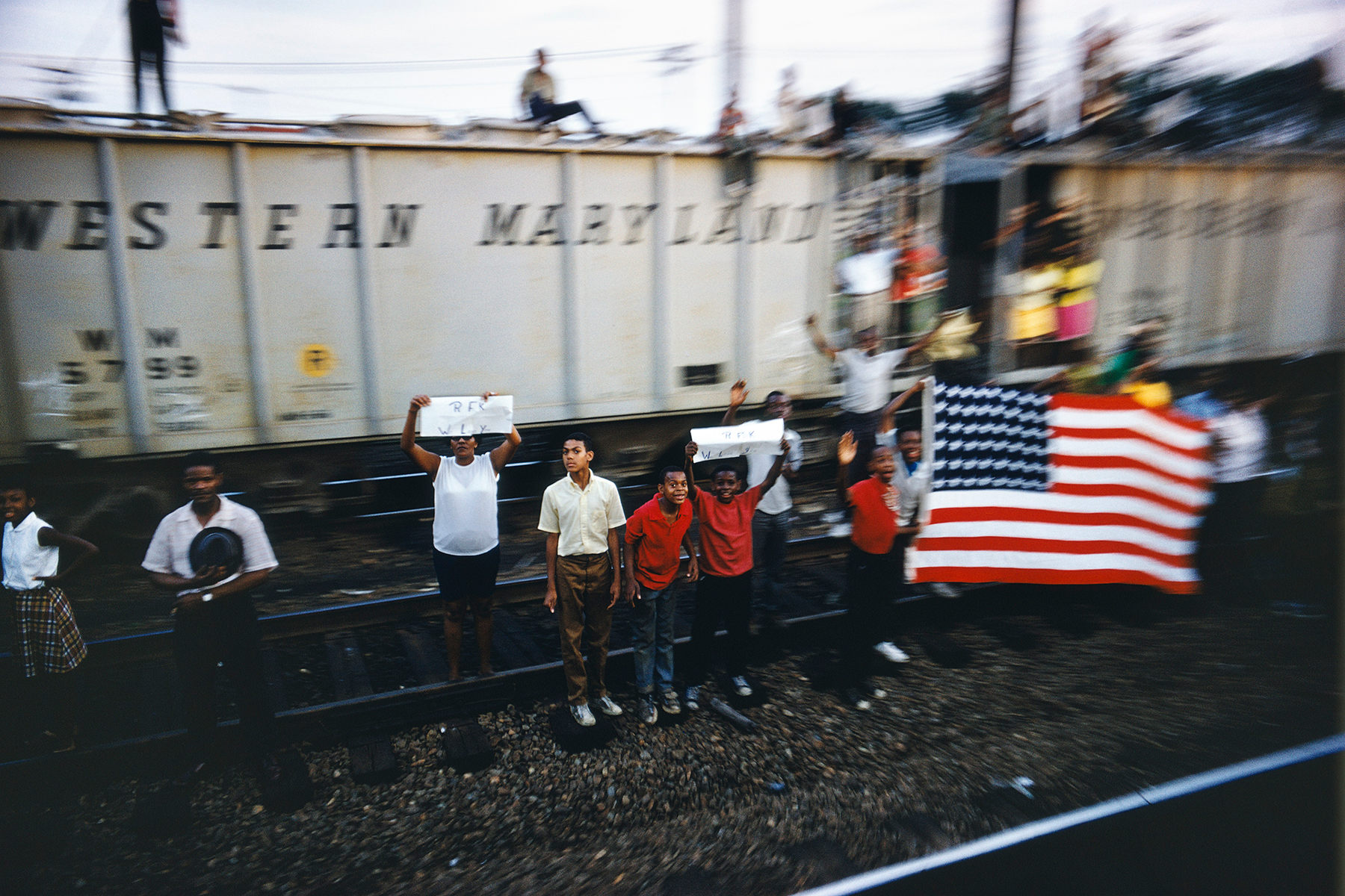 "A group of people standing along a train track holding signs that say, ""RFK We Love You"" and and American flag"