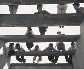 photograph of kids on slated pieces of wood from below