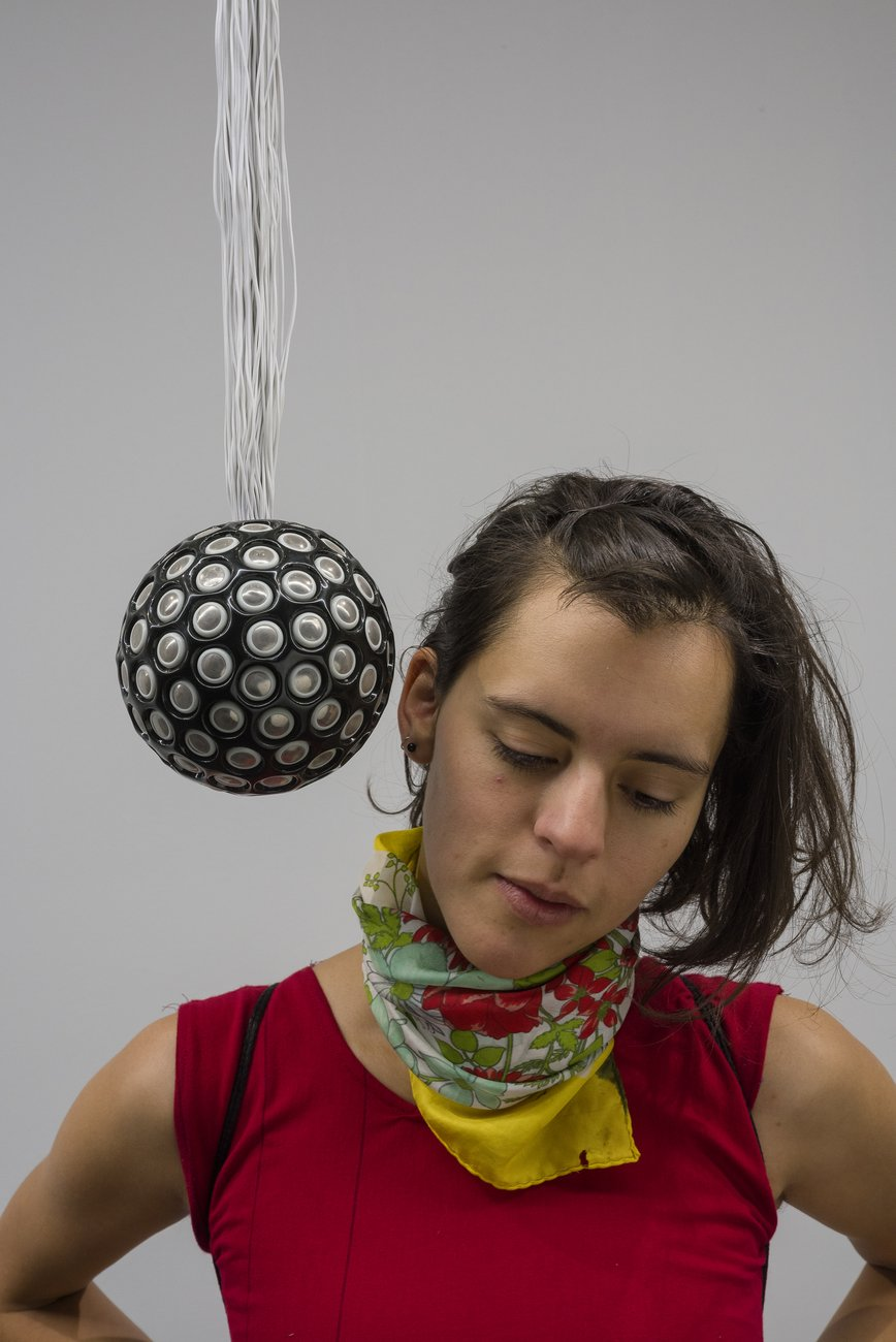 A woman stands looking down with her ear right against a hanging black orb covered in small silver speakers