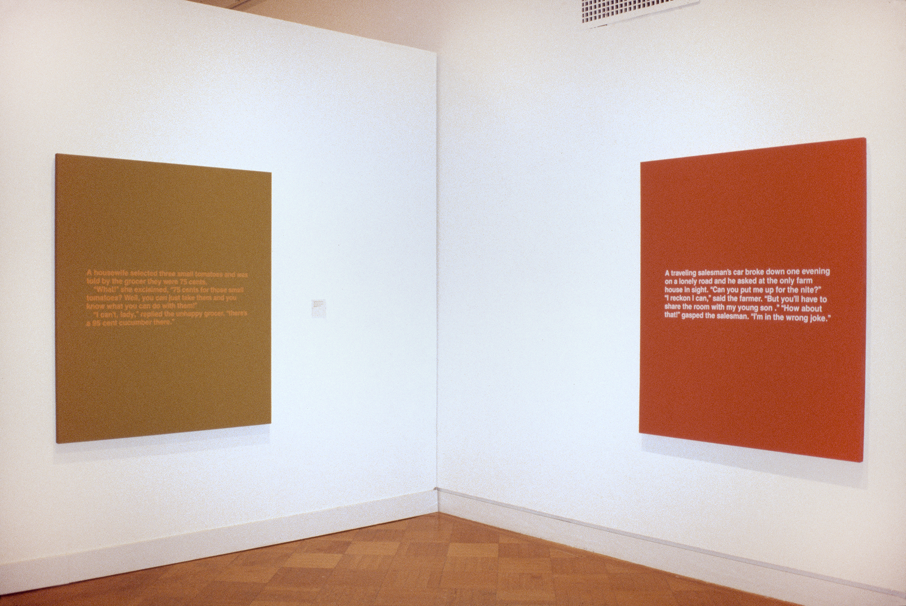 A mustard canvas and an orange canvas hanging in a gallery, each featuring blocks of white text