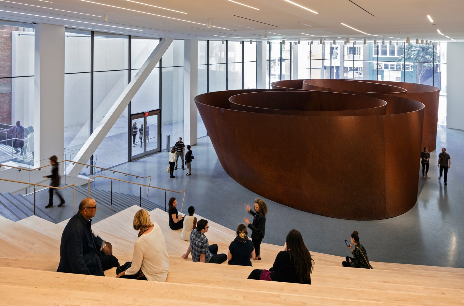 Visitors sit on steps before a massive spiraling bronze sculpture