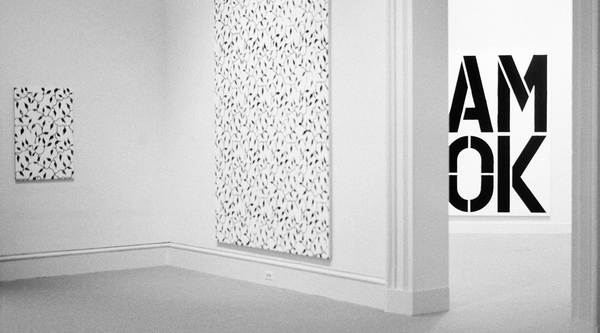 Black and white painting featuring a vine-like pattern and letters