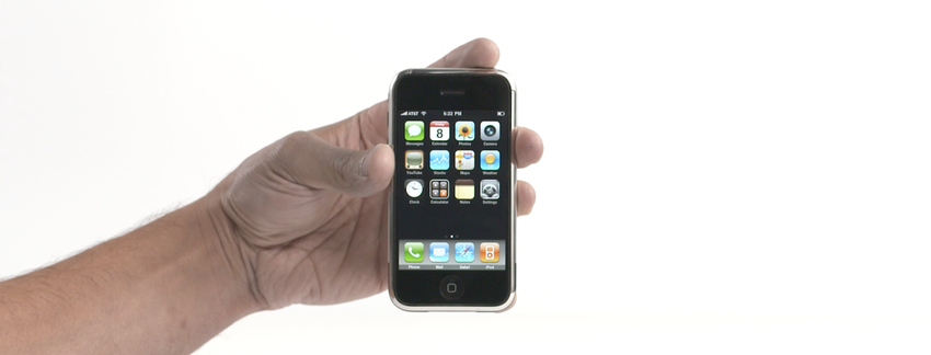 A hand holds an first generation iPhone against a white background