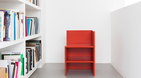 A color photograph of a square red chair sitting beside bookshelves, Donald Judd
