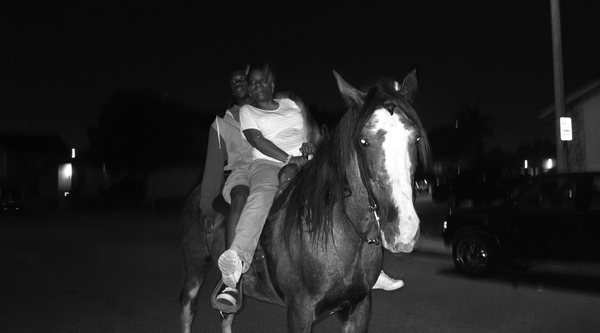 A black man and woman on a horse on a street at night