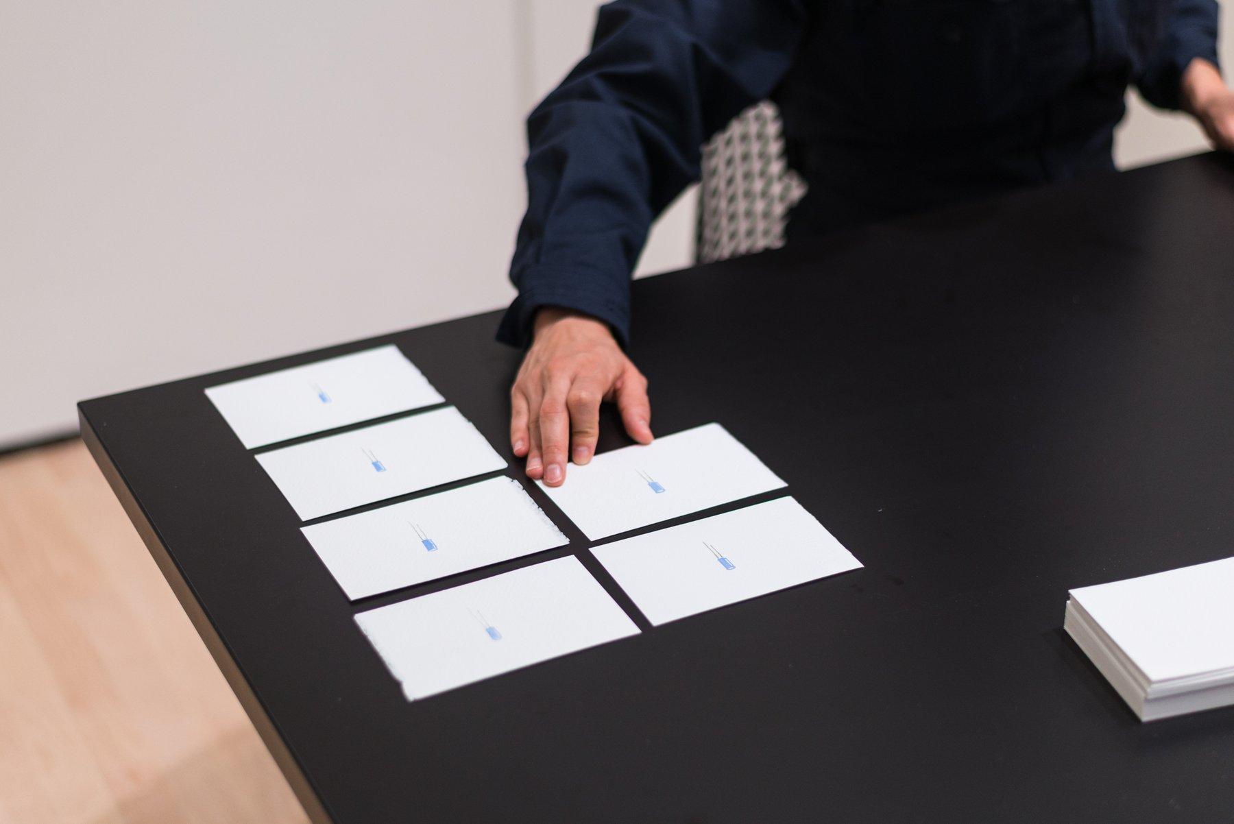 A hand arranges rectangular white cards on a black table, Munoz, Sountracks