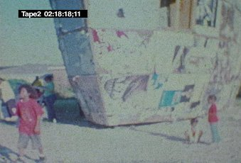 Mark Bradford, video still with two children and large structure