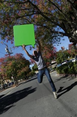 man jumping in street holding green speech bubble