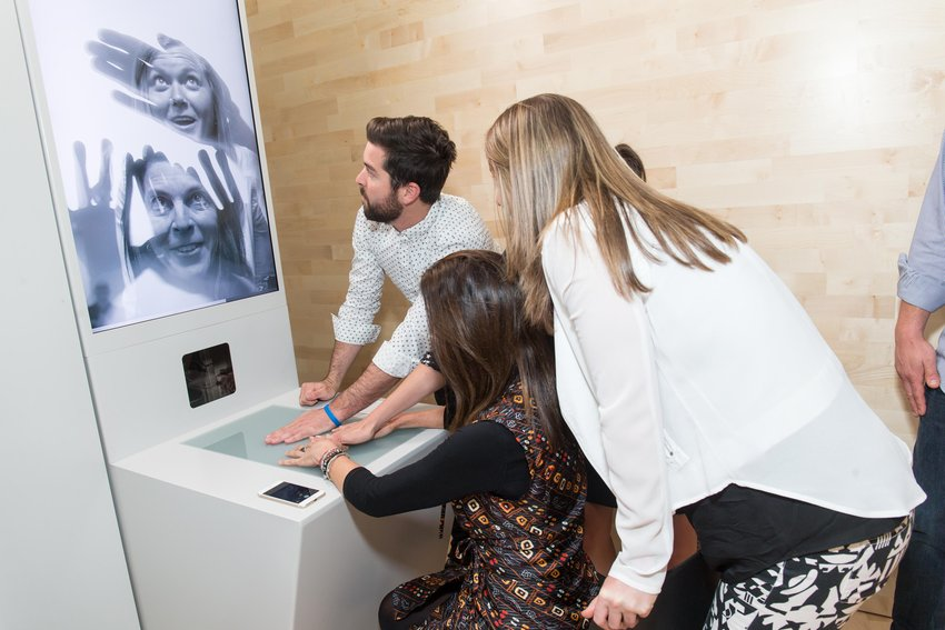 A group of people crowd around a screen as images of their faces emerge