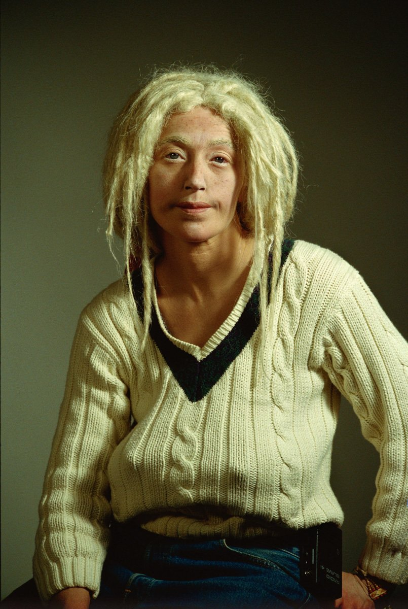 Studio-style color portrait of a woman with blonde dreadlocks and an ill-fitting, beige, cable knit sweater