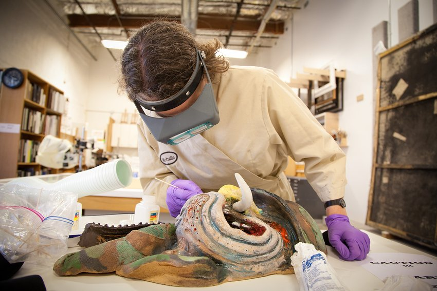 A conservator wearing a mask and touching up a sculpture
