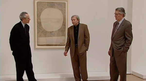 Three Caucasian men stand before a painting in a gallery, Rauschenberg