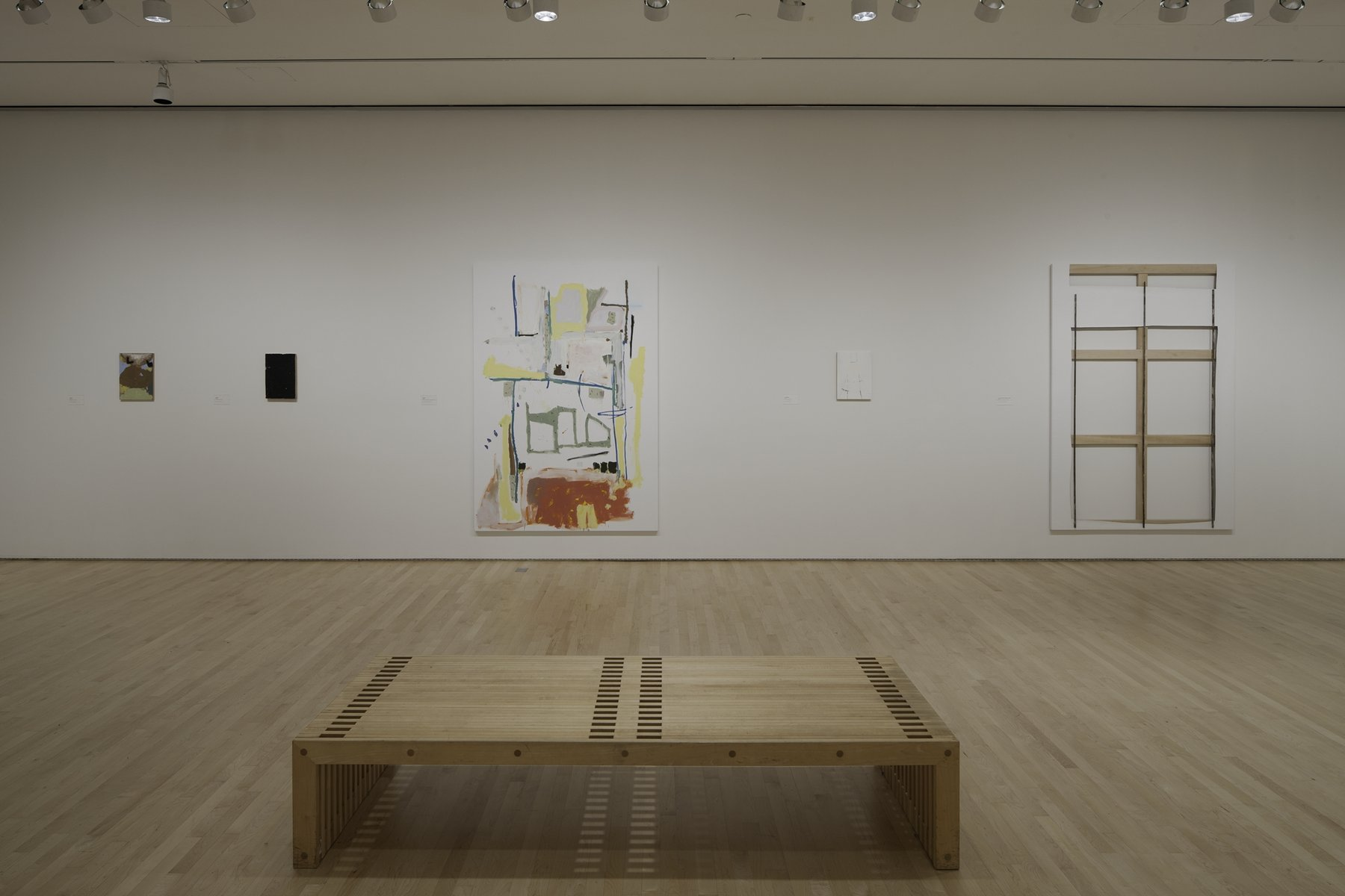 3.)	A white room with four pieces of art work by Richard Aldrich on the walls. There is a bench in the middle of the room.