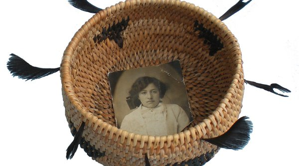 A Native American basket with a black and white photograph inside of it