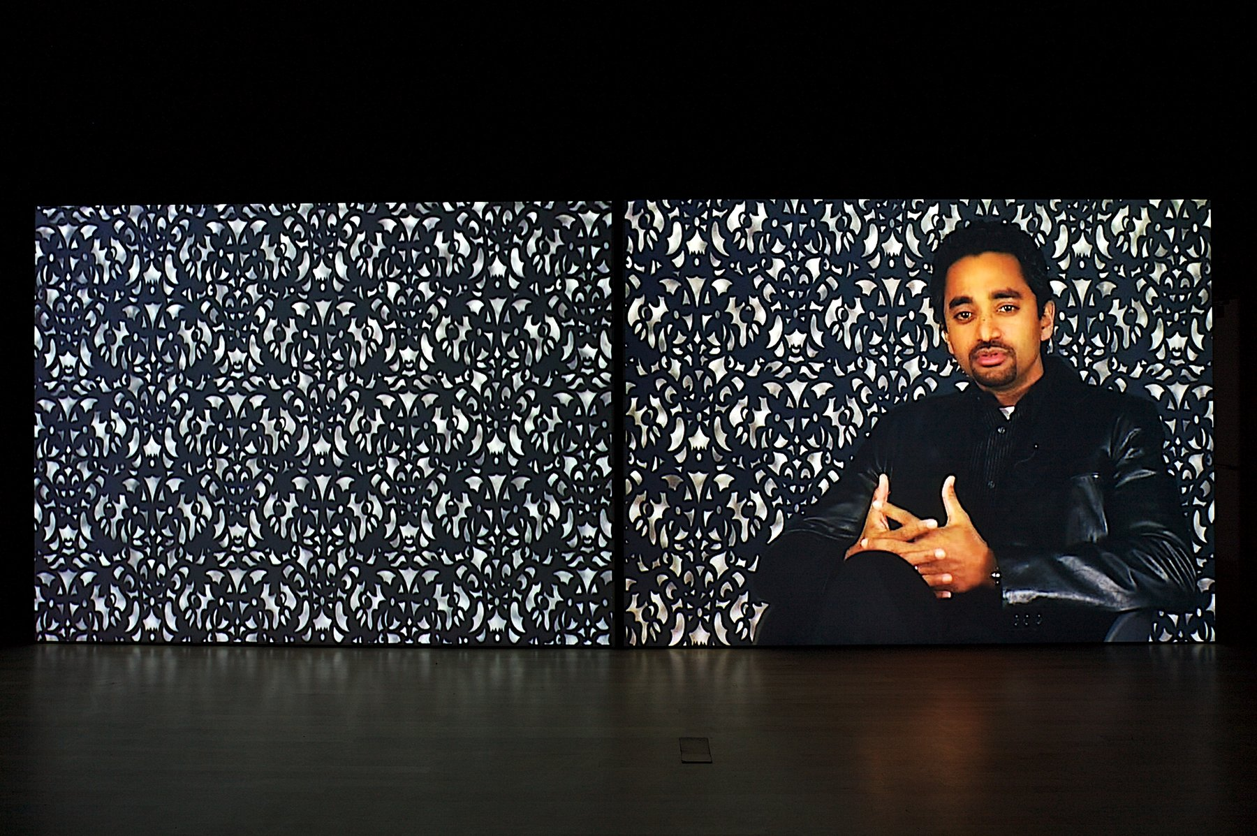 An image of a man sitting in front of a patterned wall
