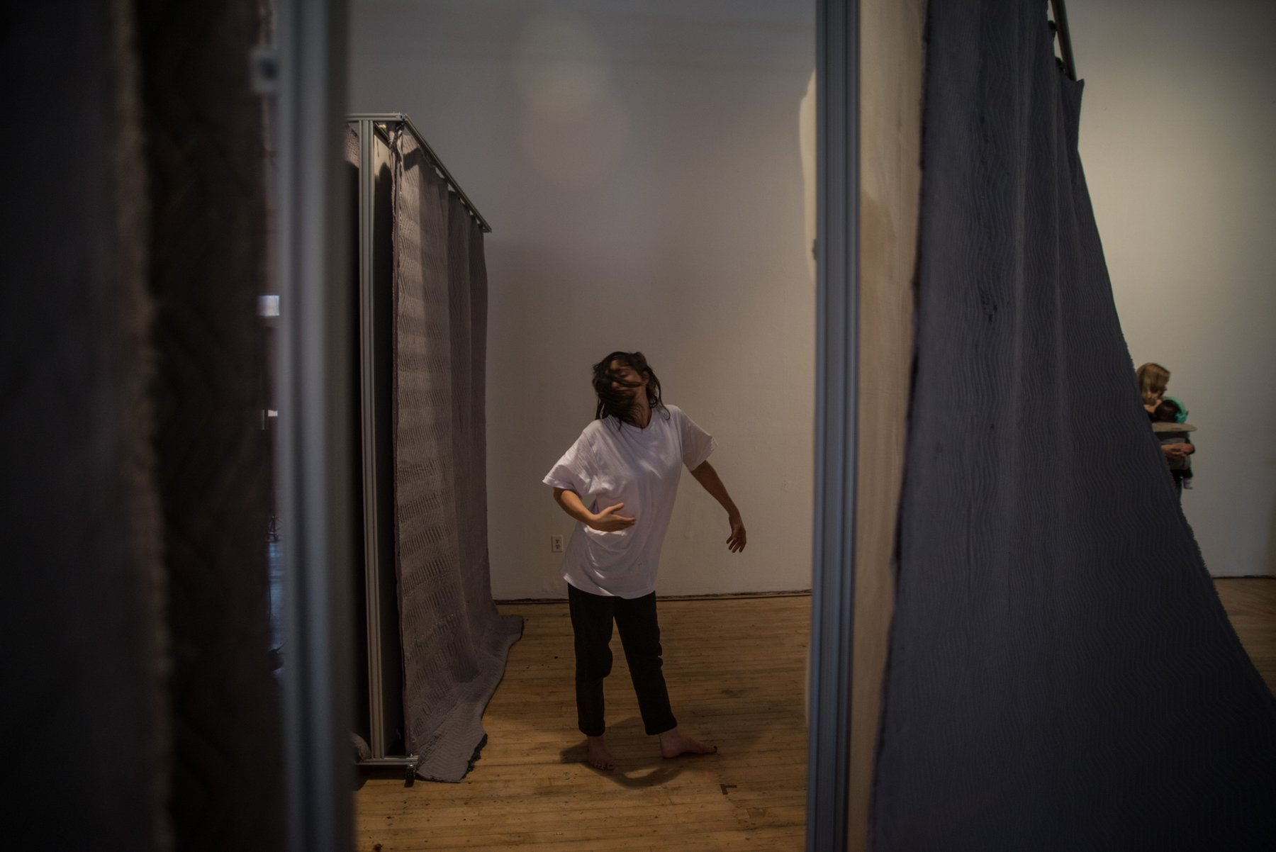 A figure with long hair and white t-shirt runs through a curtained gallery space, Gordon Soundtracks