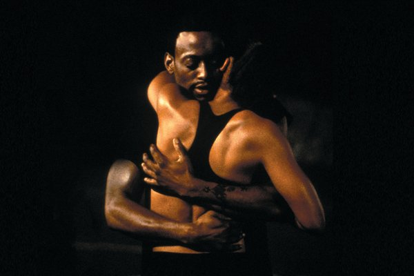 A man and woman embrace against a black background