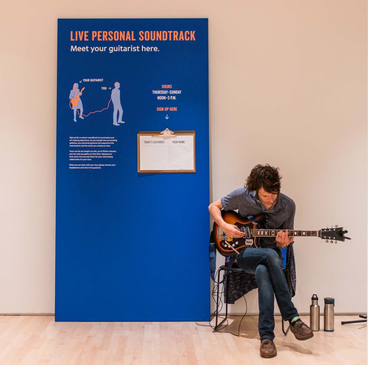 "A Caucasian man sits holding a guitar in front of a sign that says ""personal soundtracks"", Kallmyer/Allen, Soundtracks"