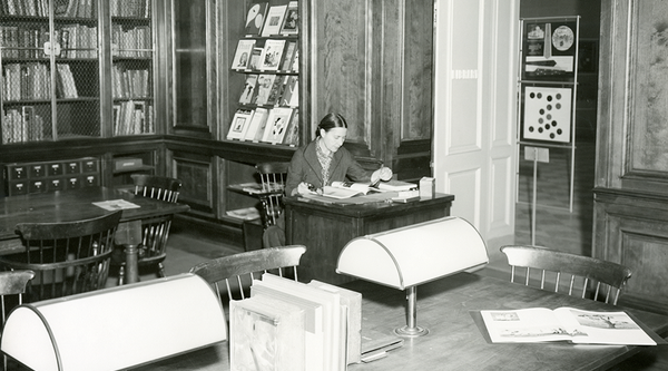 A woman seated at a large wooden table in a library