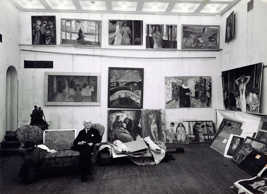 An archival black and white photograph of an elderly Caucasian man sitting in a studio surrounded by paintings