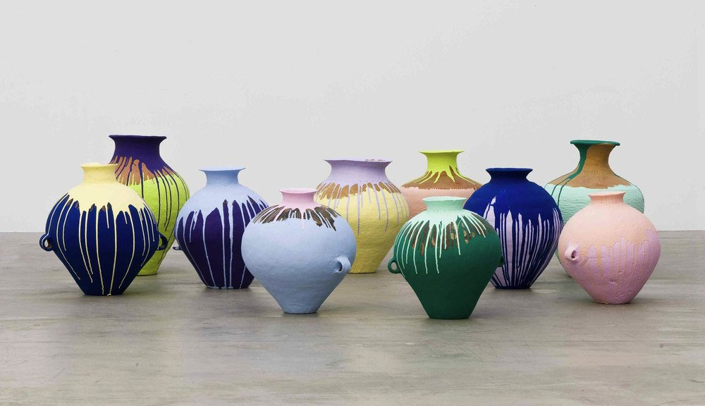 Ten clay amphorae painted with dripping, mostly pastel-colored, paint and arranged on a concrete floor