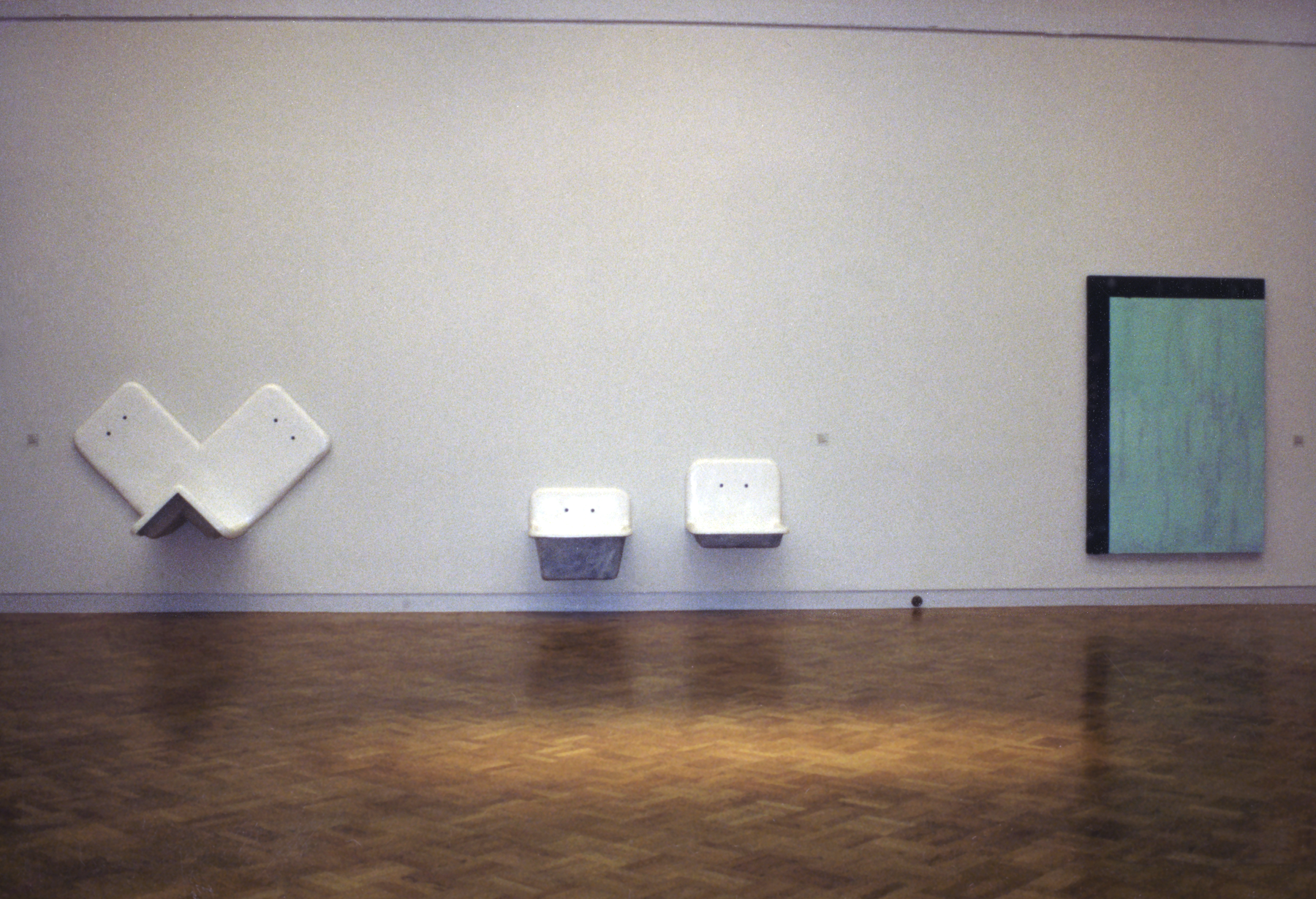 White, sink-like porcelain sculptures hang on a wall next to a large painting featuring a textured blue block and a black border around half.