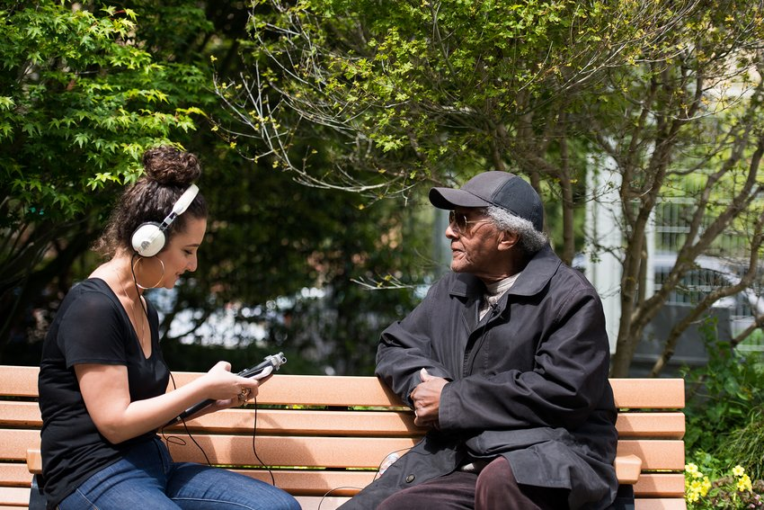 A Caucasian woman with brown curly hair wearing headphones interviews an elderly African American man on a bench, Public Knowledge