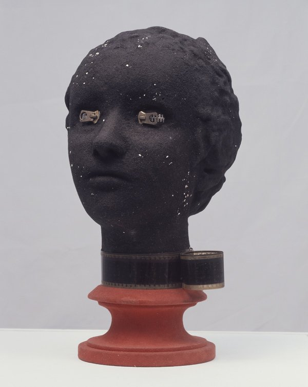 sculpture of female head with zippers over eyes