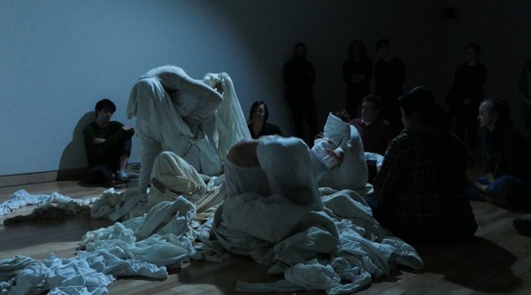 people performing in dark room with pieces of fabric