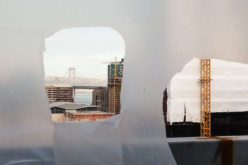 Torn hanging plastic reveals the San Francisco cityscape, including the Bay Bridge