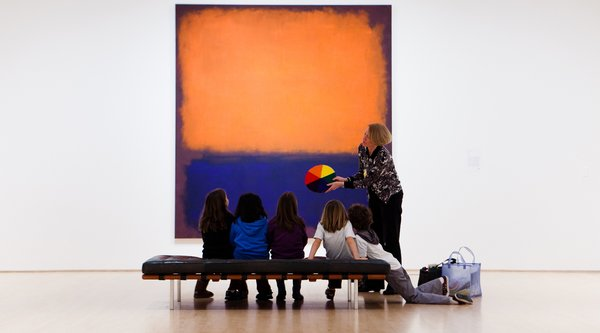 A group of students and a teacher in front of a large blue and orange abstract painting
