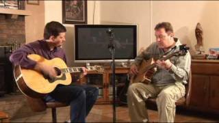 Two seated men play guitars in front of a TV in a living room