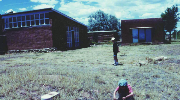 Two children play on a lawn with Adobe structures and a blue sky behind them