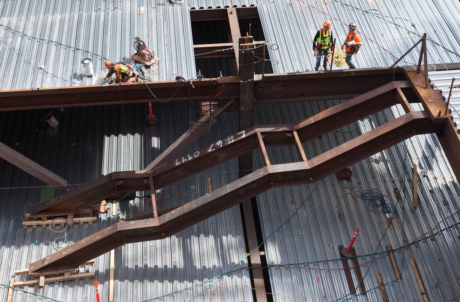 Steel beams form the beginnings of a staircase with construction workers wearing hardhats