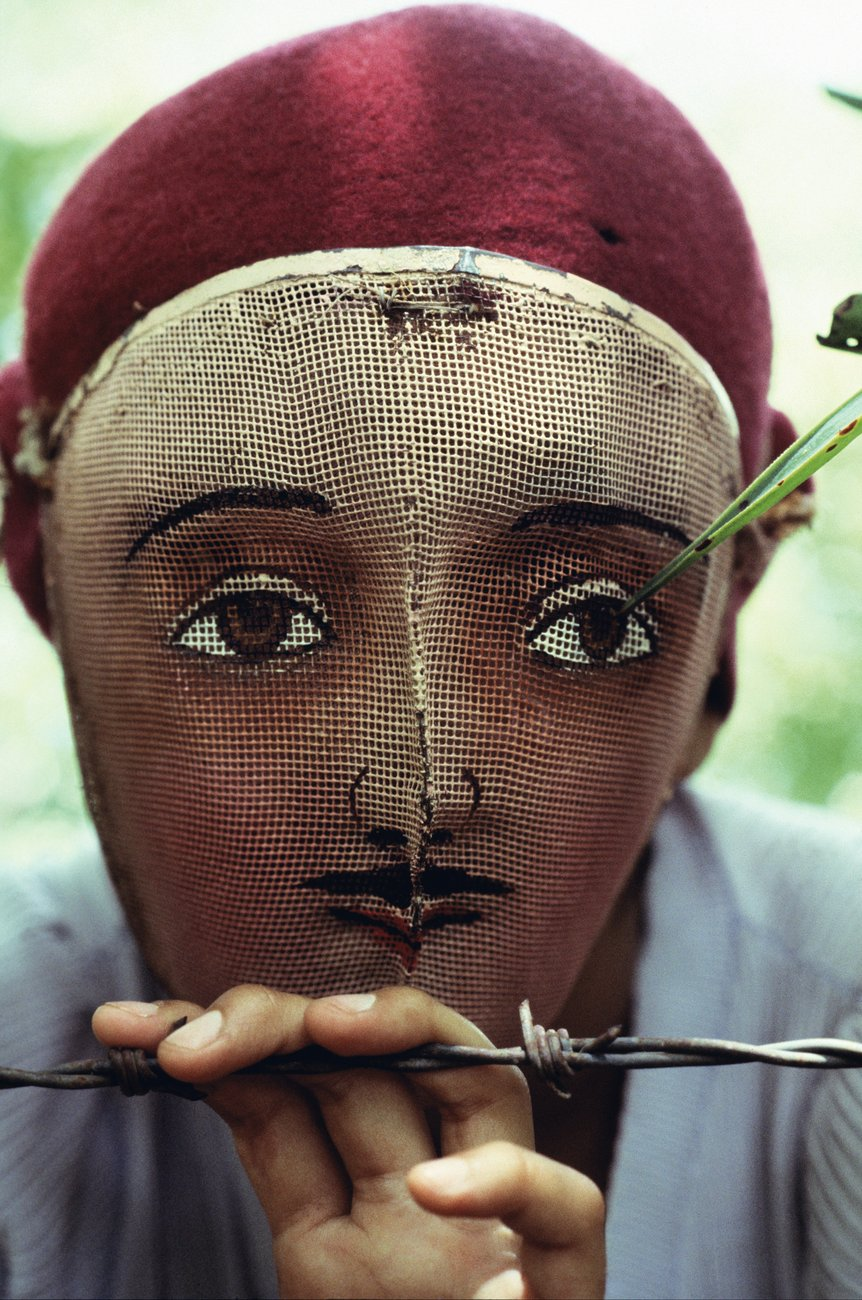 A closeup of a man or youth wearing a woven mask and burgundy beret and holding on to a barbed wire fence