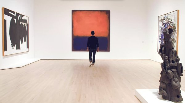 A man wearing earbuds stands before a color field painting in a gallery