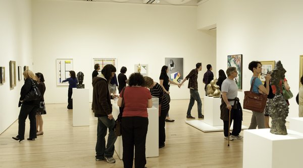People walk around a crowded gallery