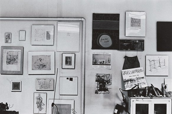A black-and-white photograph of small artworks hanging informally on a wall