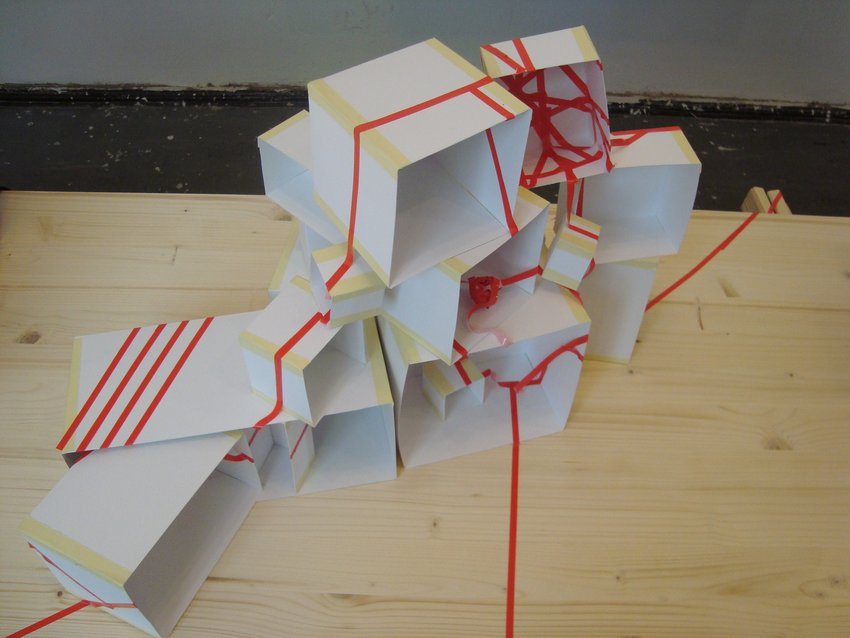 A small structure of white boxes tied up with red string