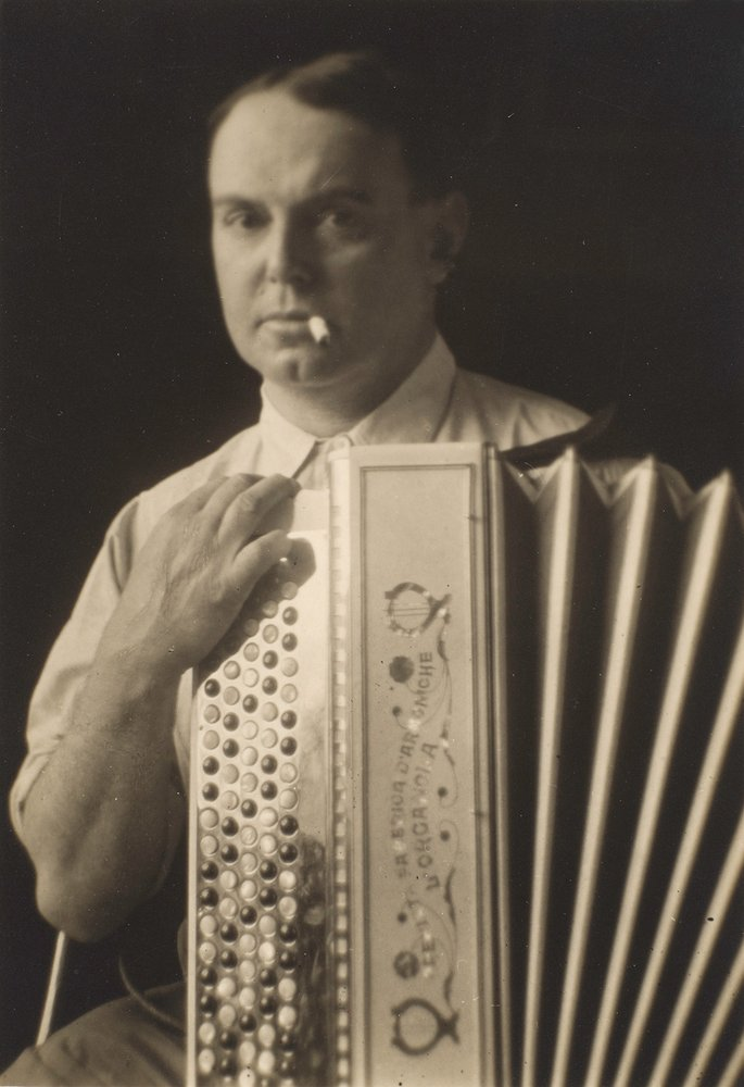 Portrait of a man holding an accordion.